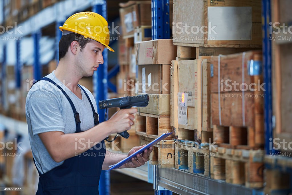 Worker checking the storages with barcode terminal in warehouse stock photo