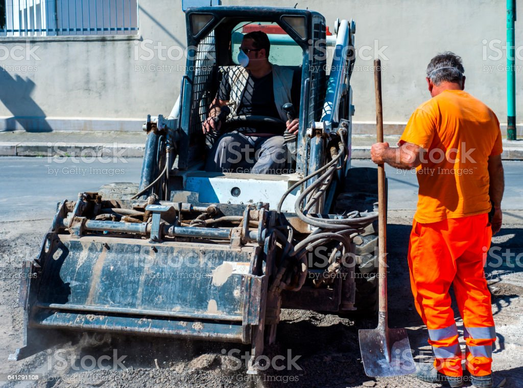 Worker checks the progress of the Milling of asphalt for road reconstruction accessory for skid steer stock photo