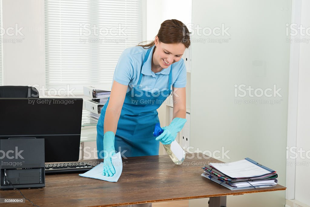 Worker Cleaning Desk With Rag stock photo