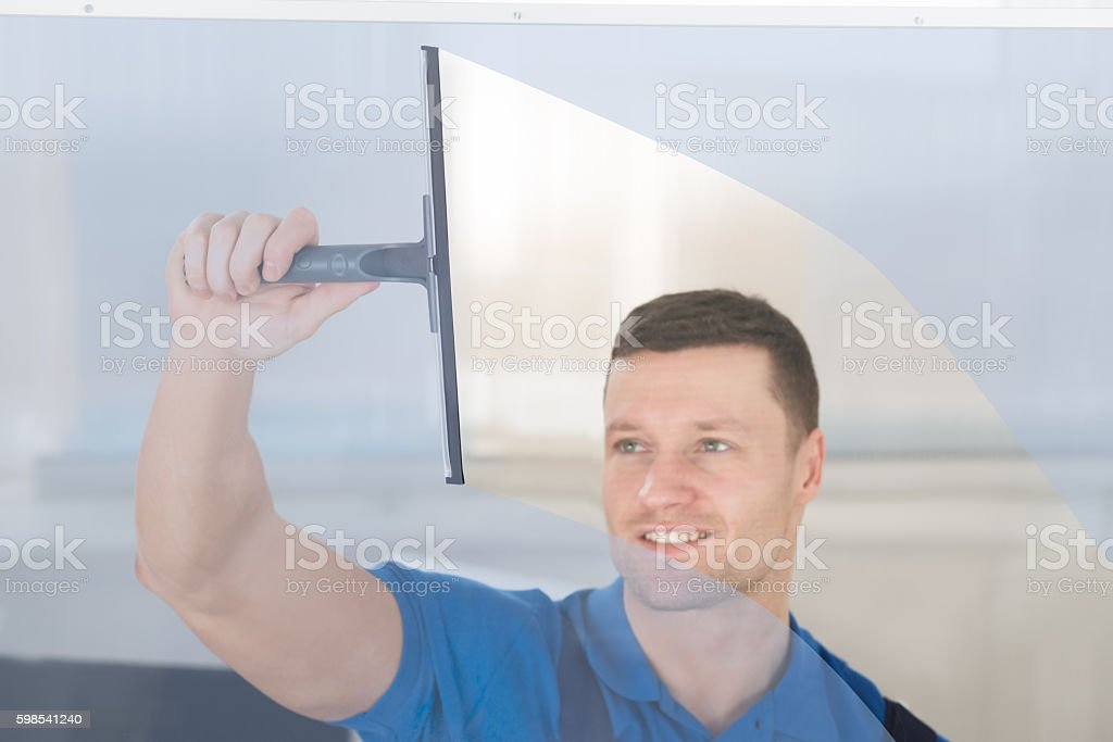 Worker Cleaning Glass Window With Squeegee stock photo