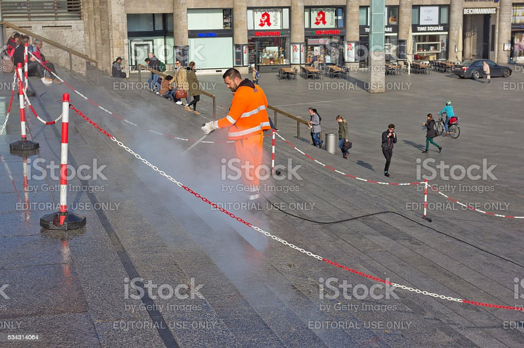 Worker cleaning steps of Cologne Cathedral, Germany stock photo