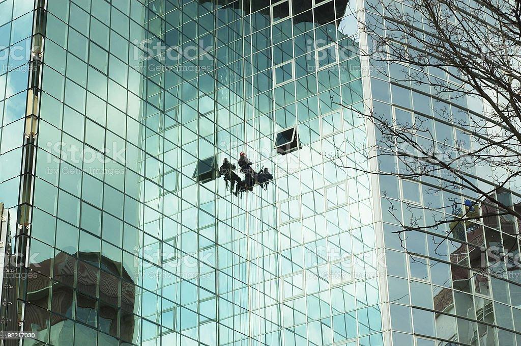 worker climbing at mirror wall stock photo
