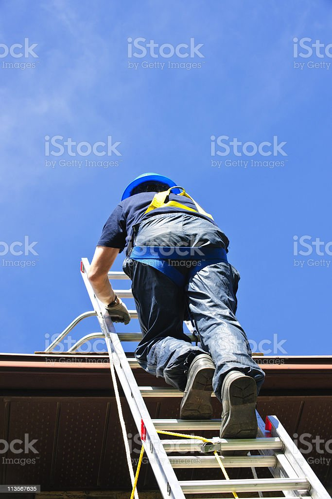 Worker climbing ladder wearing safety harness and helmet stock photo