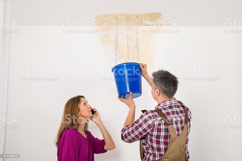 Worker Collecting Water In Bucket From Ceiling stock photo