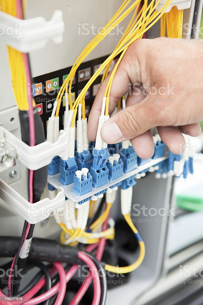 Worker Connecting Fiber Optic Wire in Cell Phone Tower Equipment royalty-free stock photo