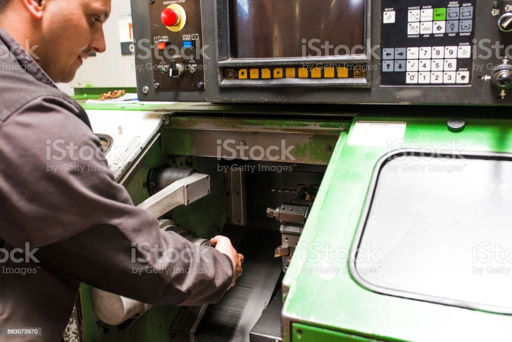 Worker control CNC machine production stock photo