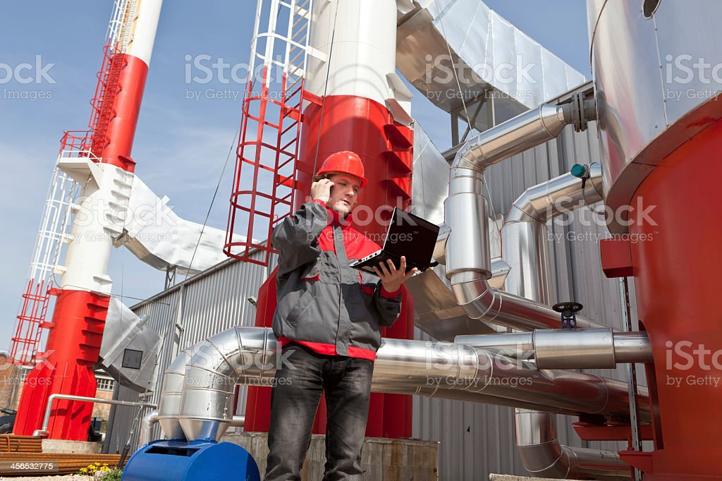 A worker controls a laptop at a refinery stock photo
