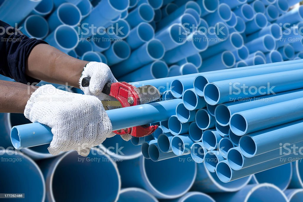 Worker cut pvc pipe in construction site stock photo