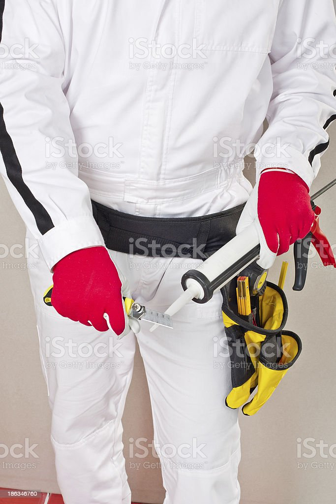 Worker cuts cap sealant silicon stock photo