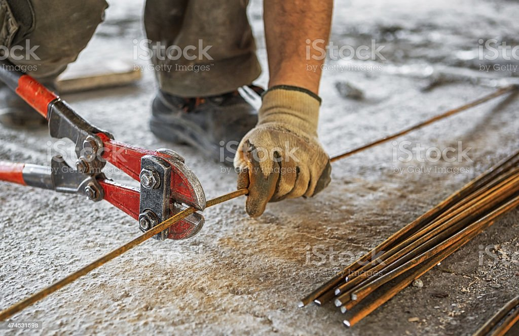 Worker cuts steel bars with bolt cutter stock photo