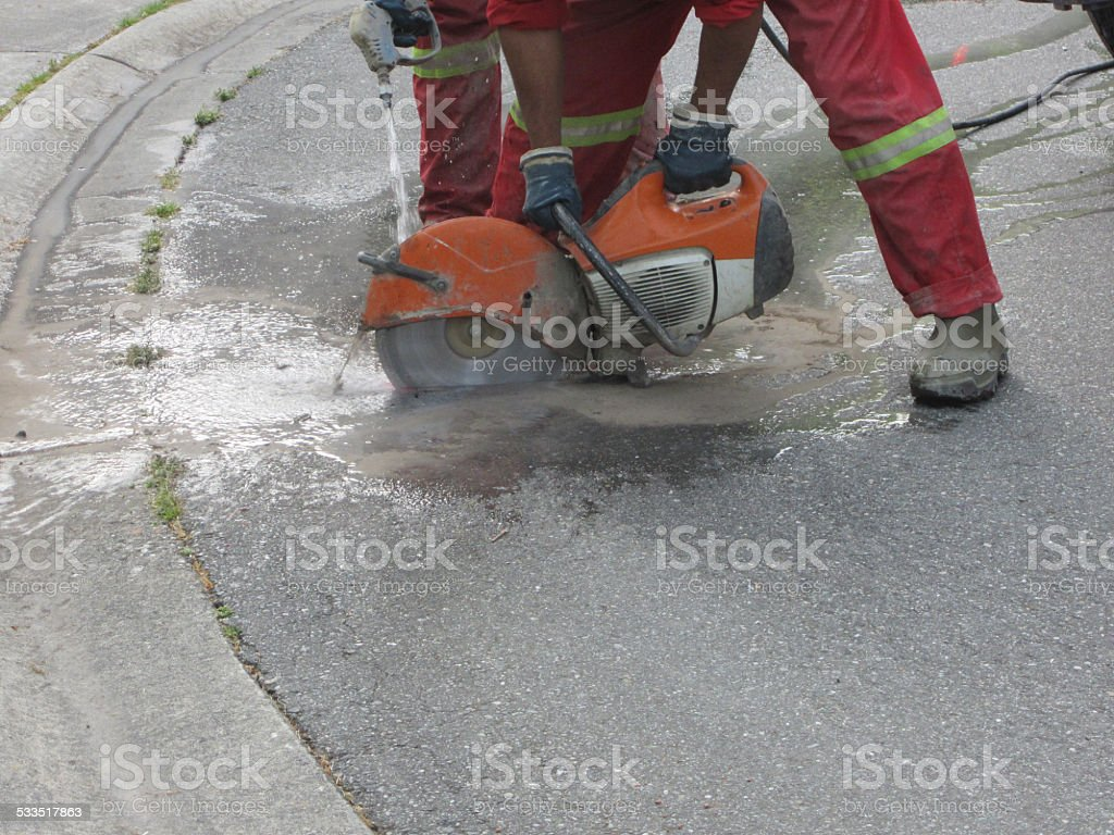 Worker cutting asphalt with a concrete saw stock photo