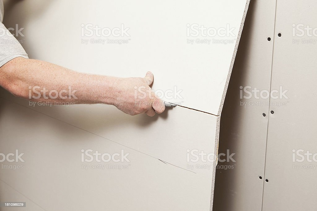 Worker Cutting Drywall with a Utility Knife stock photo