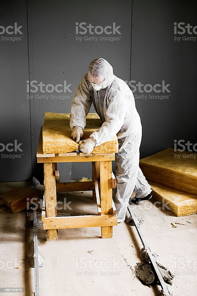 worker cutting fiberglass insulation stock photo