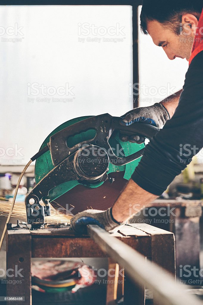 Worker cutting metal bar stock photo