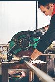 Worker cutting metal bar