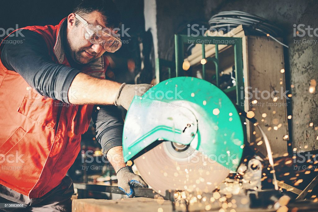 Worker cutting metal bar with grinder stock photo