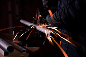 worker cutting metal pipe with angle grinder and generating sparks
