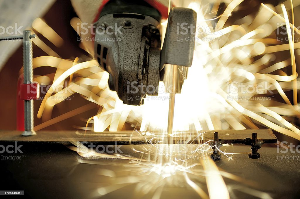 Worker cutting metal with grinder royalty-free stock photo