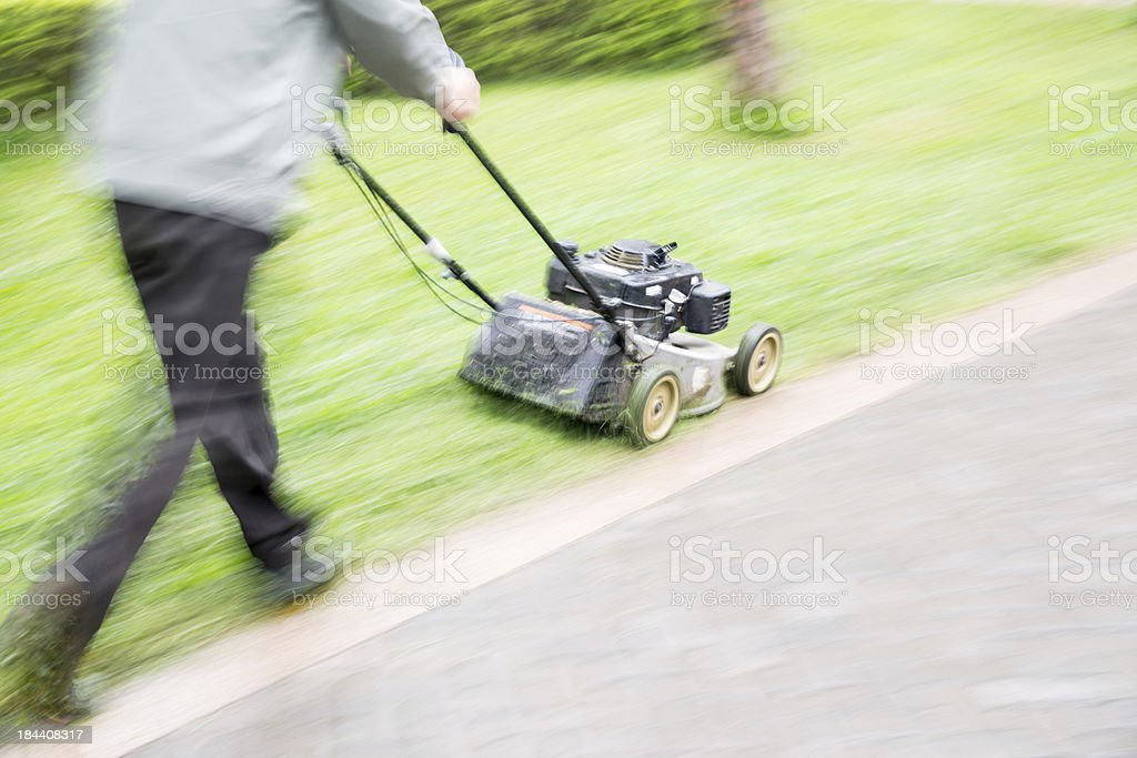 worker cutting overgrown grass with lawn mower royalty-free stock photo