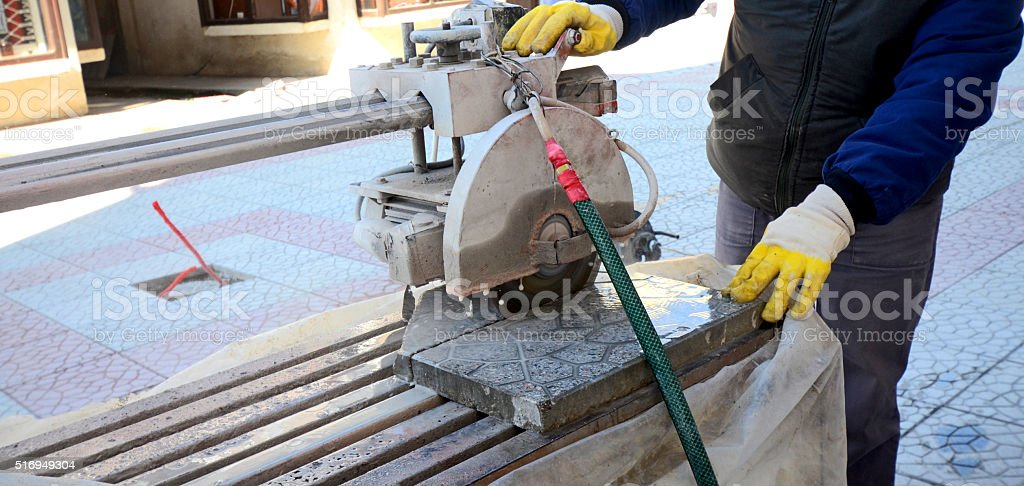 Worker Cutting Pavings Stones With a Wet Saw stock photo