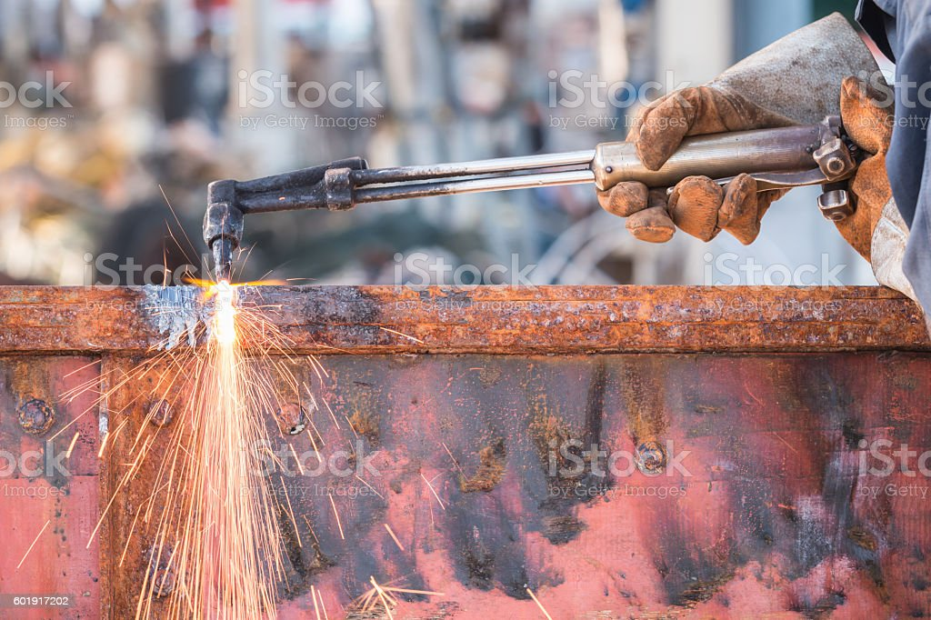 Worker cutting steel using metal torch stock photo