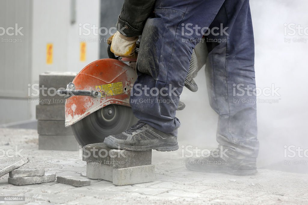 Worker cutting the brick pavers stock photo