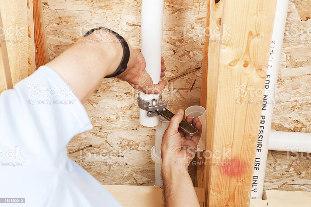 Worker Cutting Thin Wall PVC Pipe stock photo