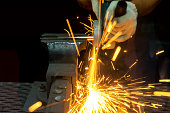 Worker cutting with grinder and welding metal with sharp sparks