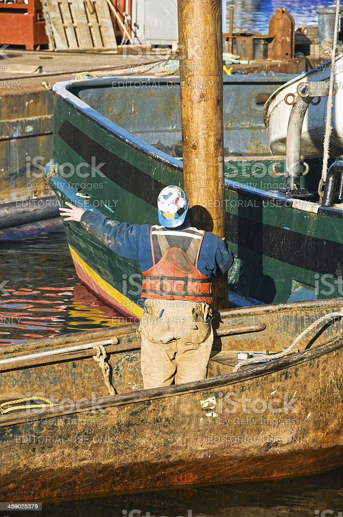 Worker directing installation of new piling at marina royalty-free stock photo