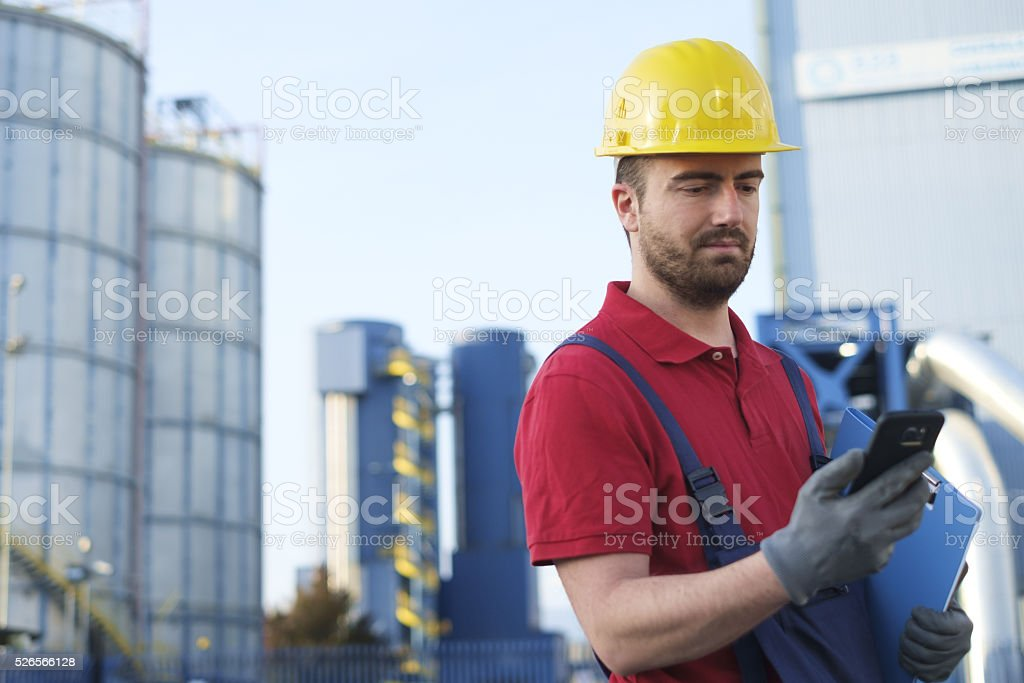 worker dressed in safety overalls outside a factory stock photo
