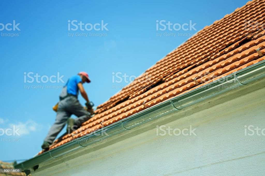 Worker drilling on the roof stock photo
