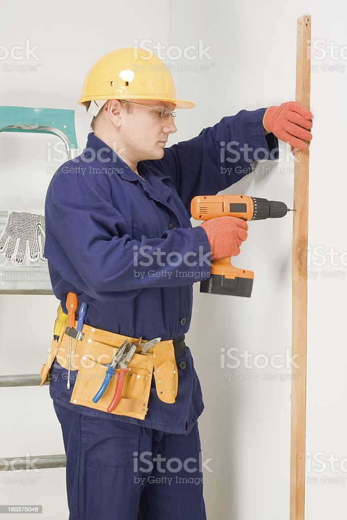 Worker drills a wooden rail royalty-free stock photo