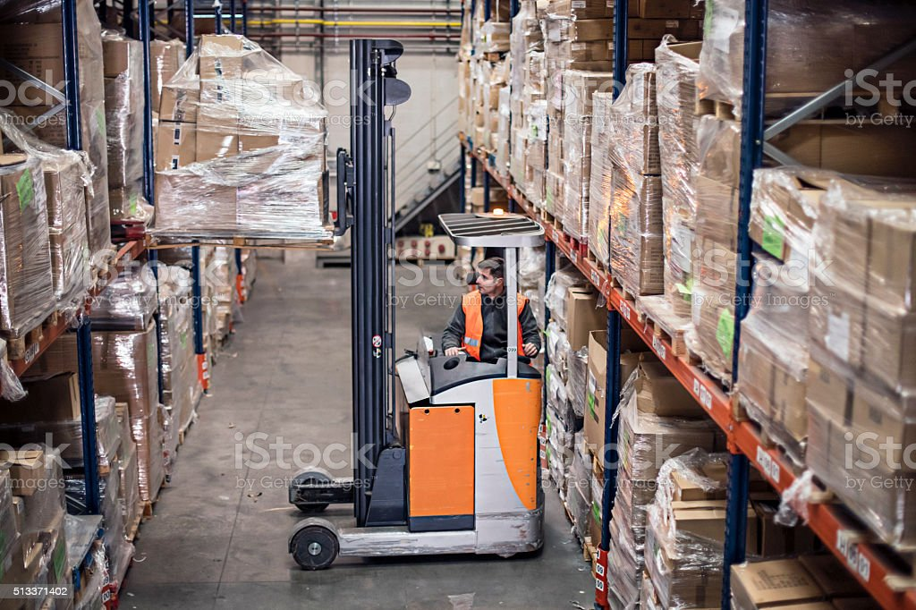 Worker driving a forklifts carrying cardboard box in warehouse stock photo