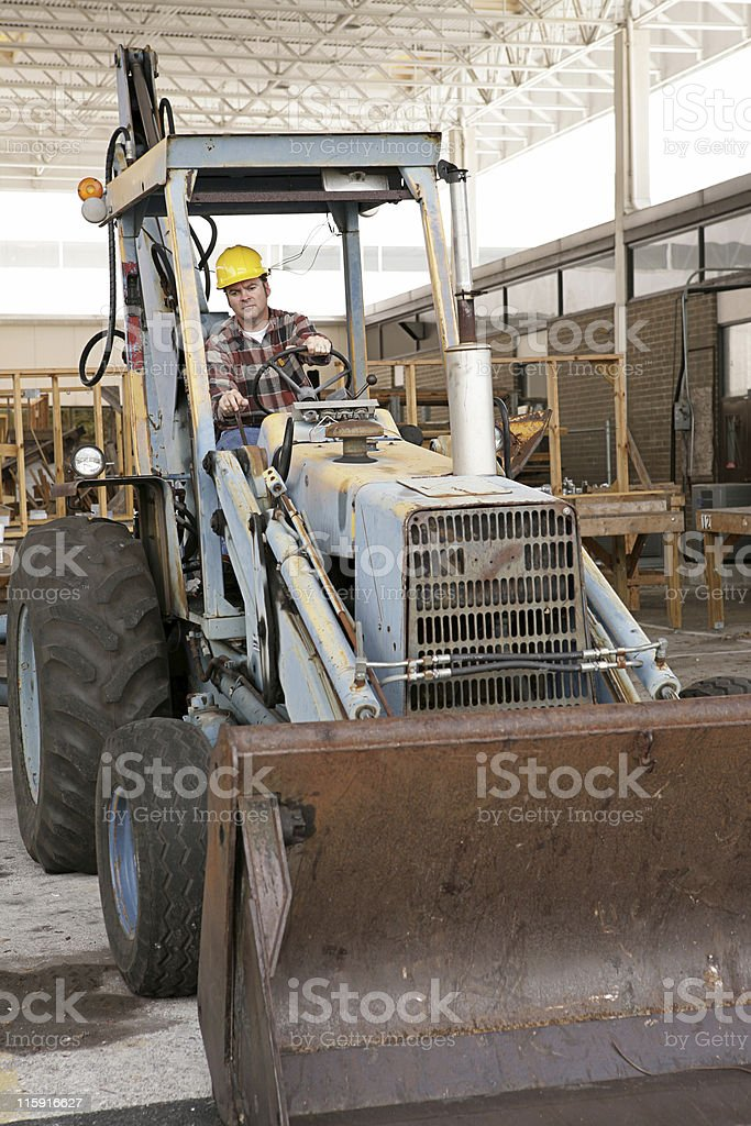 Worker Driving Backhoe royalty-free stock photo