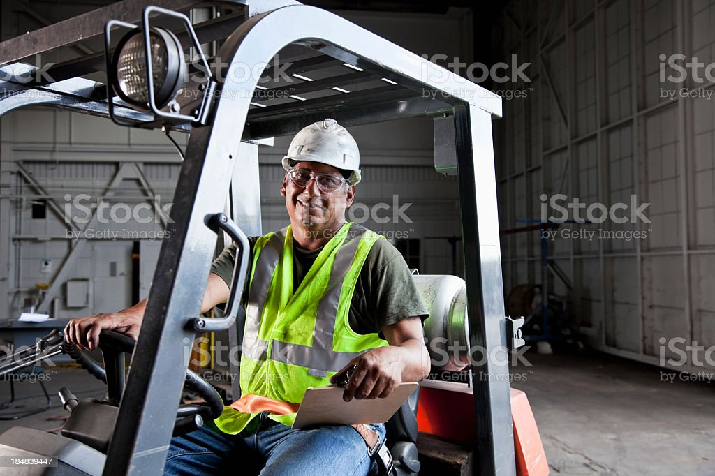 Worker driving forklift stock photo