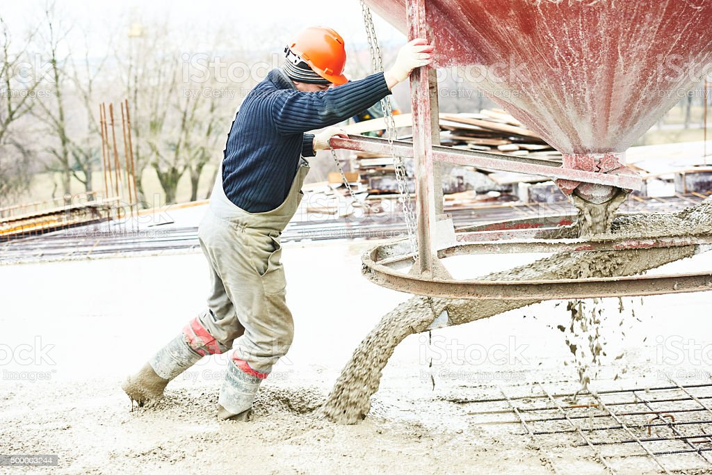 Worker during concrete pouring into formwork stock photo