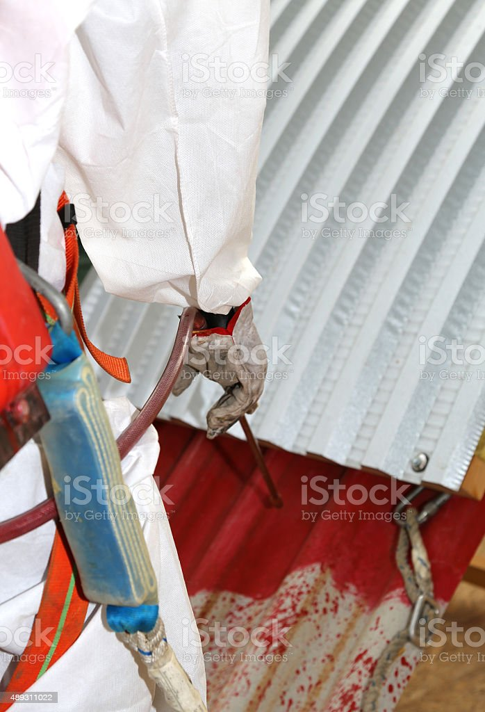 worker during the remediation of asbestos from the roof stock photo