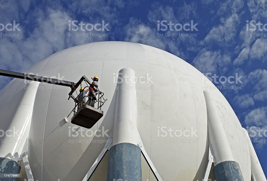 Worker elevated on a cherry picker in front of large sphere stock photo