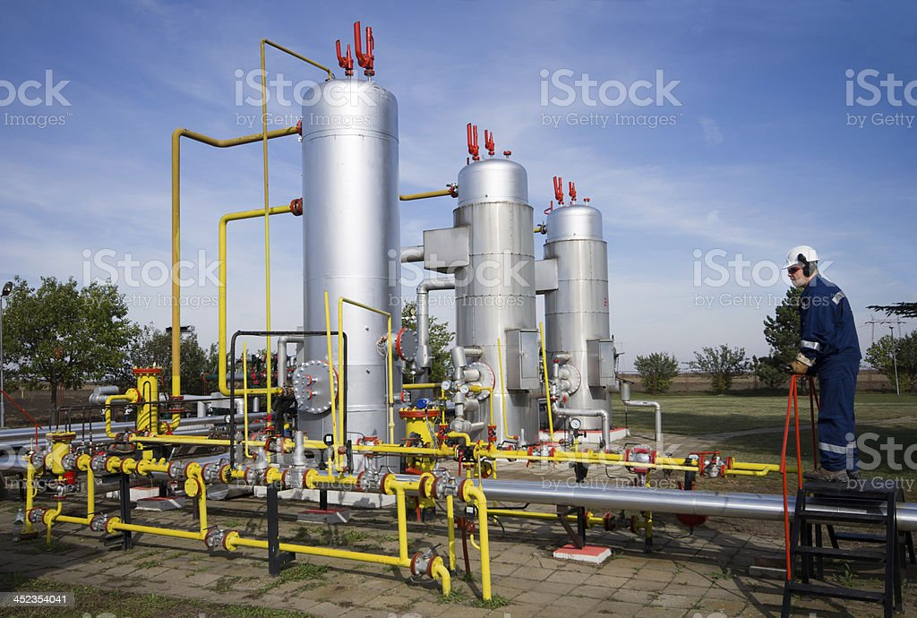 A worker examining oil pumps and pipelines stock photo