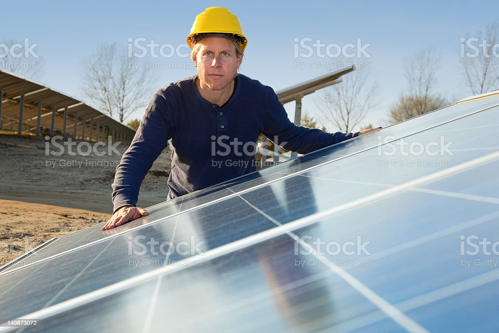Worker examining solar panels stock photo