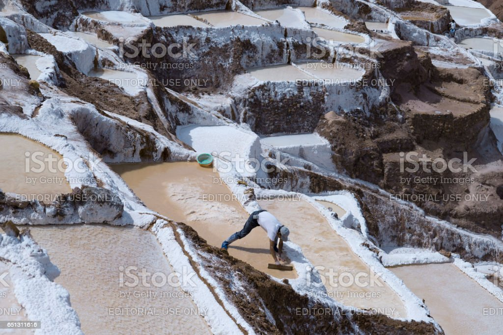 Worker extracting manually salt from the Maras salt ponds located at the Peru's Sacred Valley. October 18, 2012 - Maras, Peru stock photo
