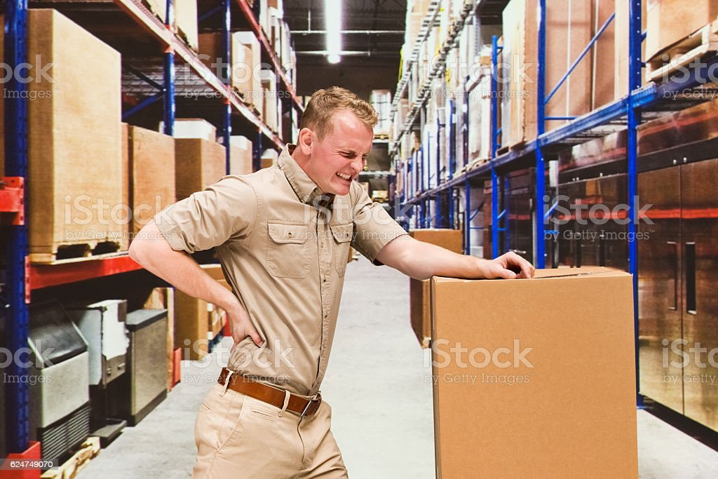 Worker feeling back pain in warehouse stock photo