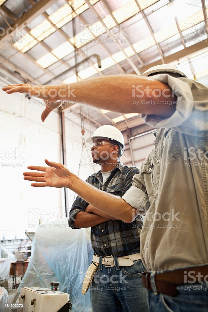 Worker gesturing at manufacturing facility royalty-free stock photo