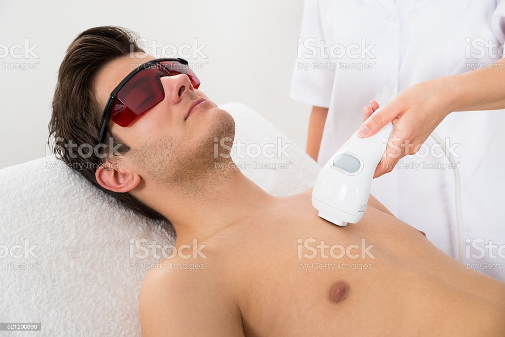 Worker Giving Man Laser Epilation stock photo