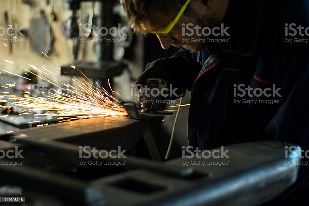 Worker grinding a metal part in his workshop. stock photo