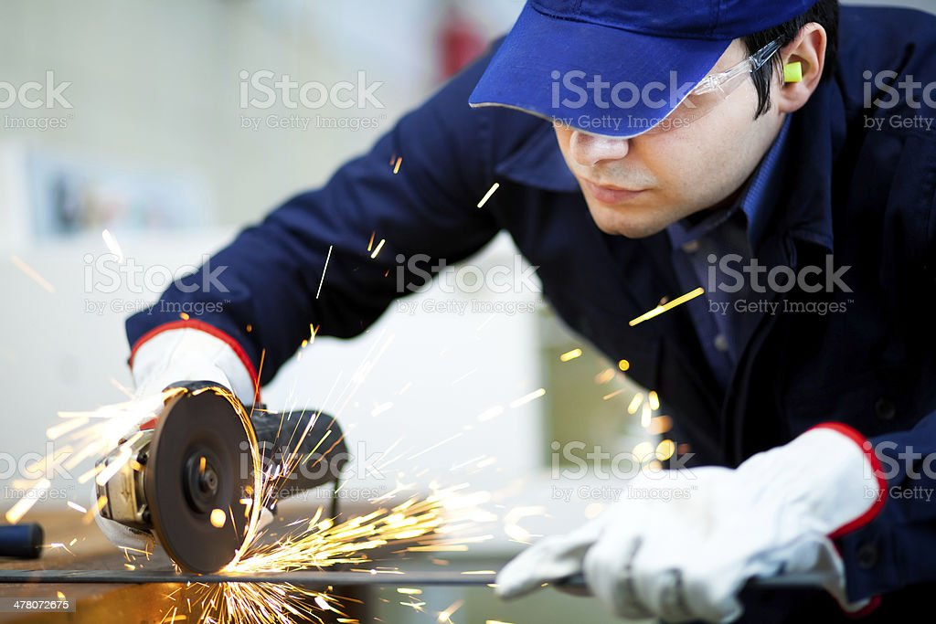 Worker grinding a metal plate stock photo