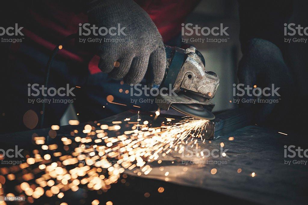 Worker grinding metal close up shot stock photo