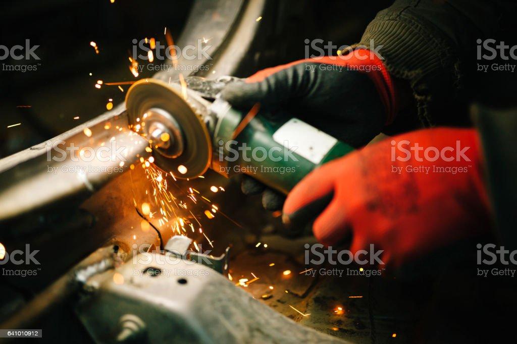 Worker grinding metal stock photo