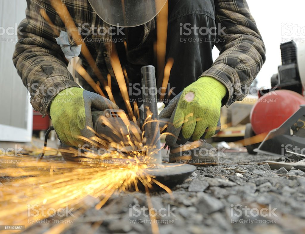 Worker Grinding Metal.  Sparks fly. stock photo