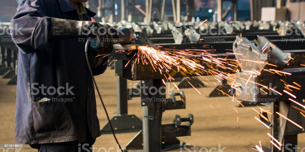 Worker grinding metal with angle grinder stock photo